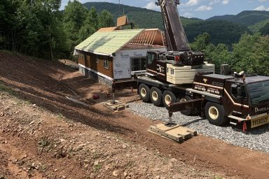 a crane setting the roof on a prefab login cabin in parson west virginia
