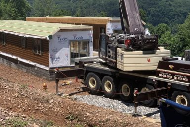 a crane setting the two pieces of a prefab log cabin together with the beautiful mountains of parson west virginia in the background