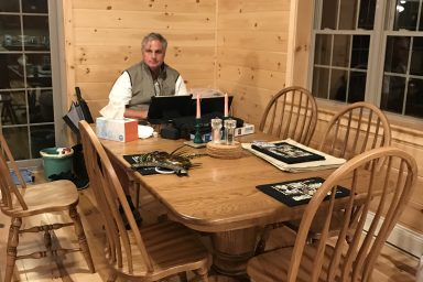a man enjoying his new dining room inside his gorgeous prefab log cabin in parson west virginia