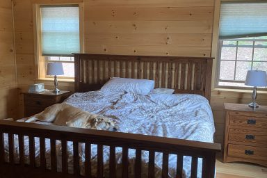 a nice sized master bedroom inside of a gorgeous wooden prefab log cabin