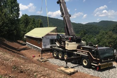 placing the new prefab log cabin together in parson west virginia