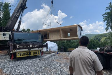 postioning the modular pieces of a prefab cabin in the prepared site in parson west virginia