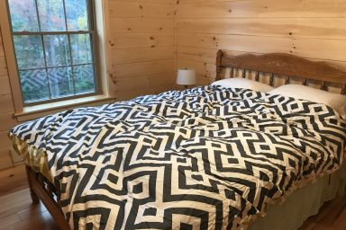 second bedroom with decorative wooden bed inside of a prefab log cabin