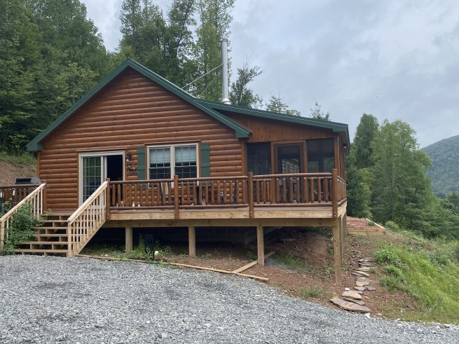 stunning brand new prefab log cabin in the spring in parson west virginia with green foilage all around