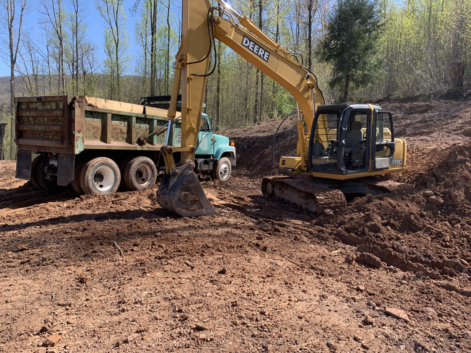the beginning work of site preparation for a prefab log cabin with a bulldozer and dump truck