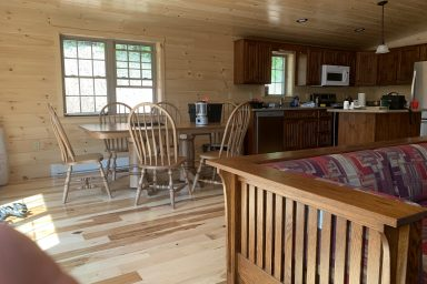 the open dining and kitchen area inside of a completed prefab log cabin