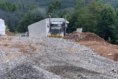 tractor trailer bringing prefab log cabin to parson west virgina prepared site