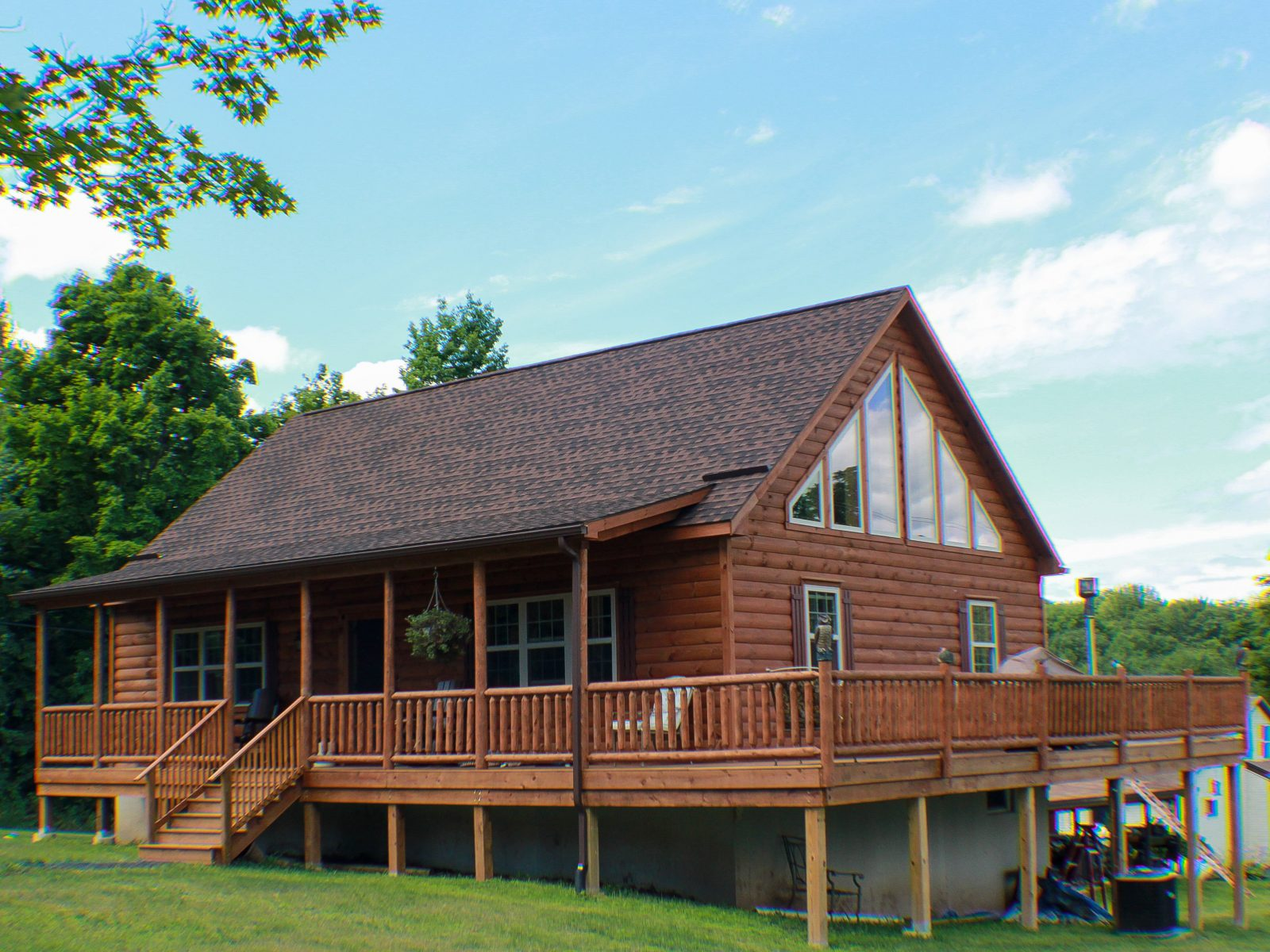 lofted log cabin with a wraparound porch 1